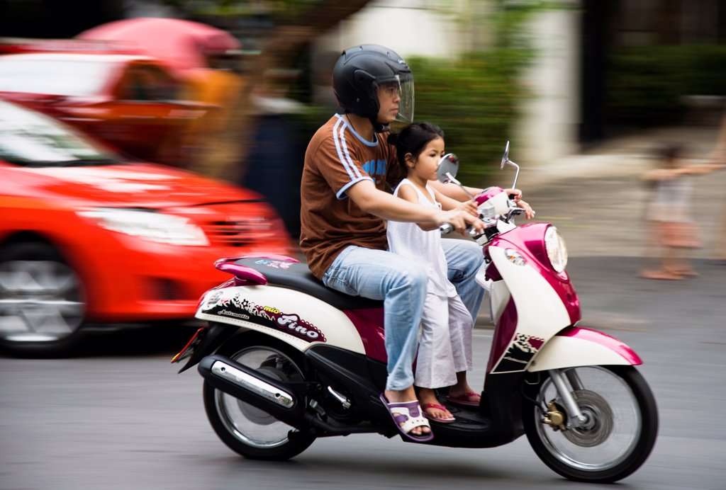 Thailand, Bangkok, Father with young daughter on motorcycle pass brightly coloured taxis. : Stock Photo