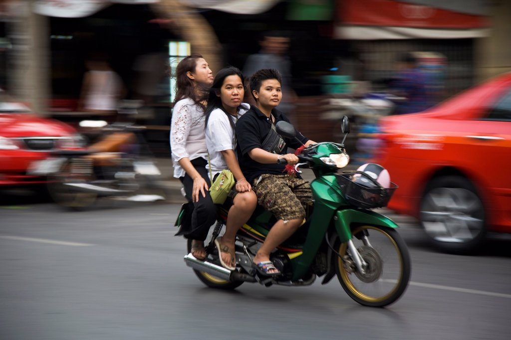 Stock Photo: 1850-45677 Thailand, Bangkok, Young Thai women on motorcycle without helmets, helmet in shopping basket blurred motion.