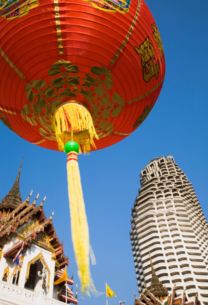 Stock Photo: 1850-45698 Thailand, Bangkok, Wat Yannawa temple roof and unfinished apartment block from 1990s Asian financial crash with red lanterns at Chinese New Year.