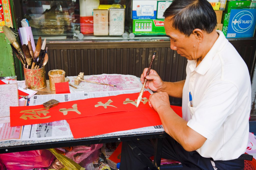 Stock Photo: 1850-45718 Thailand, Bangkok, Calligrapher painting Gold characters on red paper, auspicious colours for Chinese New Year.