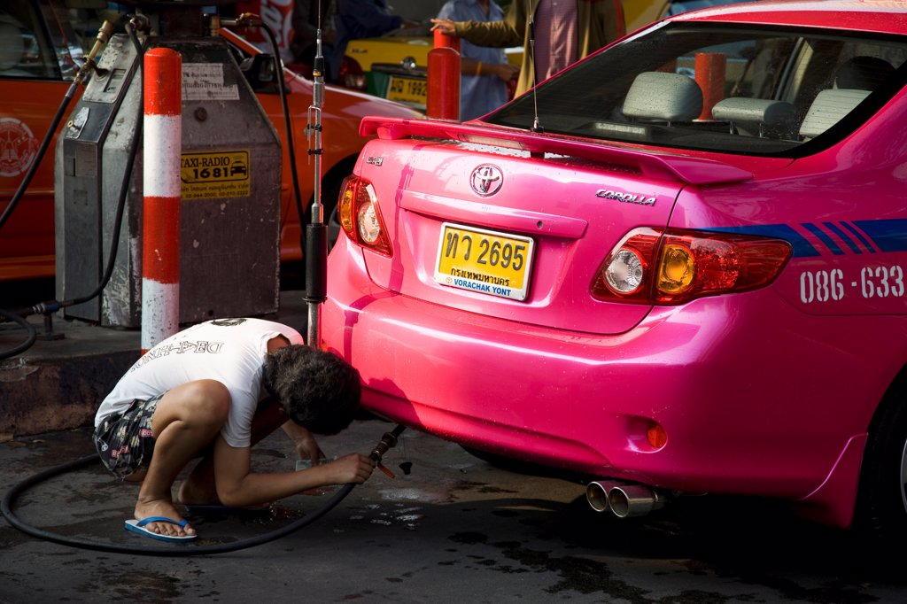Stock Photo: 1850-45734 Thailand, Bangkok, Pink metered taxi cab being refuelled with LPG gas pipe.
