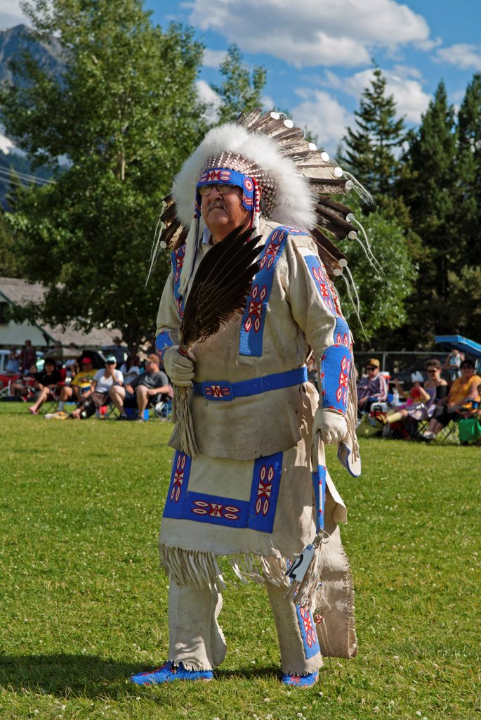 Canada, Alberta, Waterton Lakes National Park, Buckskin Dance at the Blackfoot Arts & Heritage Festival Pow Wow organized by Parks Canada and the Blackfoot Canadian Cultural Society, This dance is only for Blackfoot Chiefs and Elders and is a slow war dance, Blue sky with white clouds, Tourists in lawn chairs watching spectacle. : Stock Photo