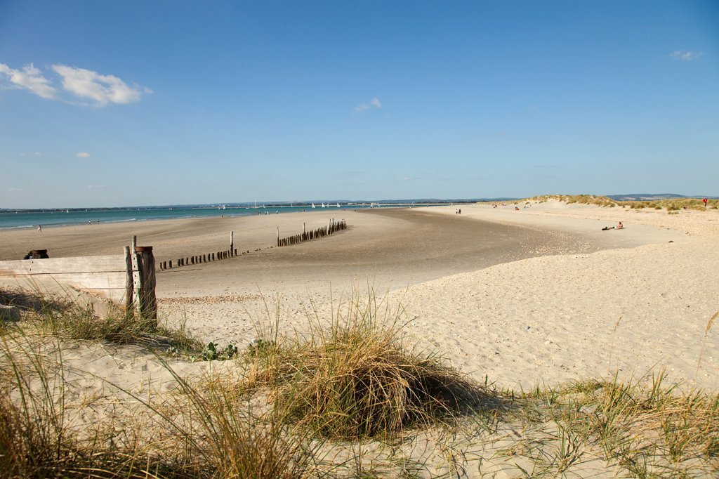 England, West Sussex, West Wittering Beach, View across sand dunes towards beach and sea at East Head. Sunshine and blue sky. : Stock Photo