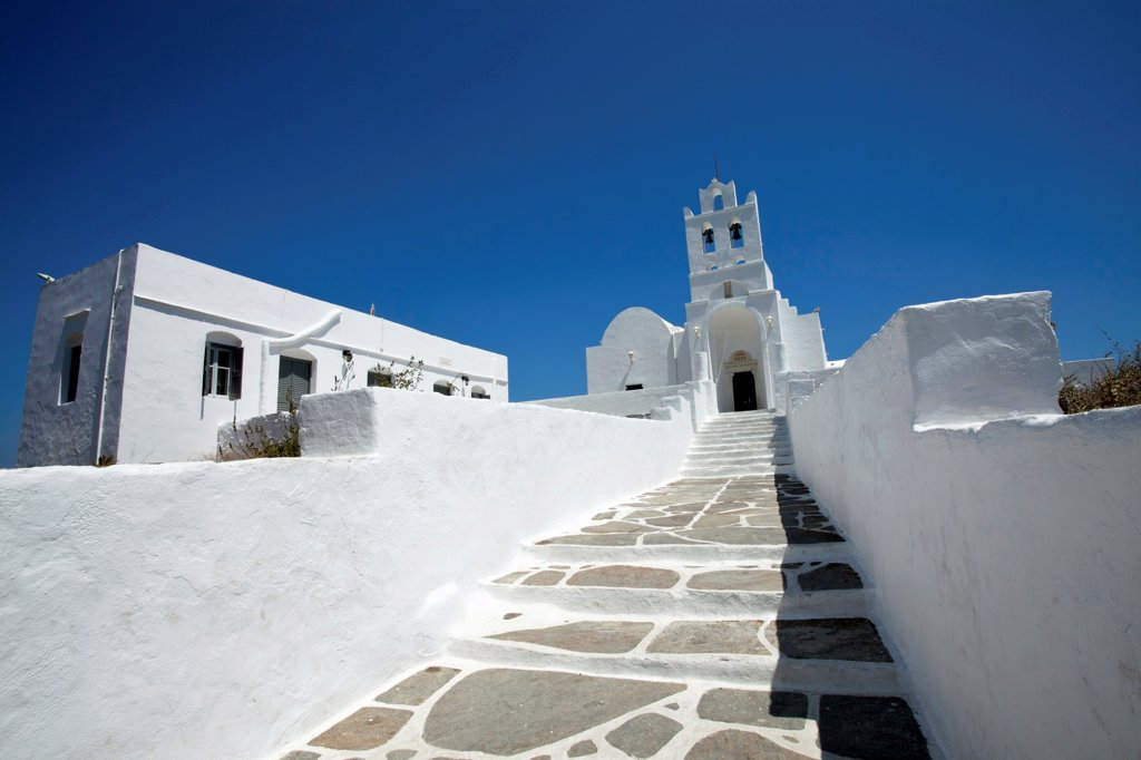 Stock Photo: 1850-45991 Greece, Cyclades Island, Sifnos Island, Landscape format low angle photograph of the church inside Chrissopigi monastery which is build on the top of a cliff nearby Platis Yalos village and it is famous for housing the miraculous icon of Panagia Chrissopigi.