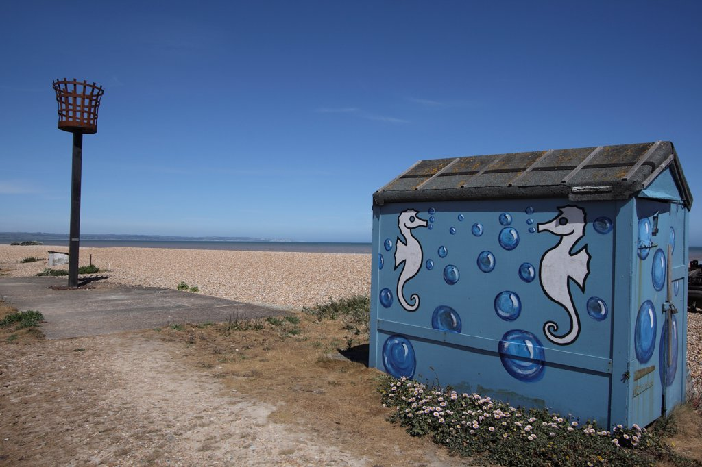 Stock Photo: 1850-46006 England, Kent, Romney Marsh, Littlestone Beach, Hut painted with Seahorse design and seafront torch beacon.
