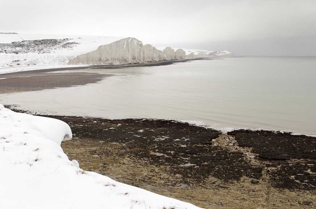 England, East Sussex, Seven Sisters, Snow covered chalk cliffs viewed from the coastguard cottages at Cuckmere Haven. : Stock Photo