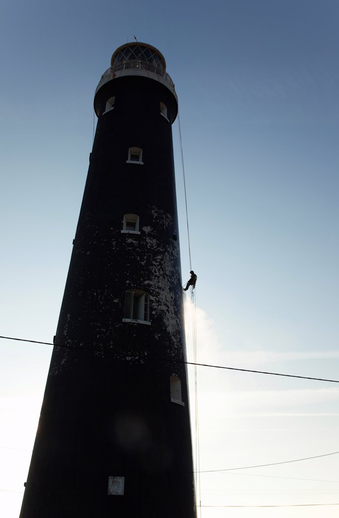 Stock Photo: 1850-46073 England, Kent, Romney Marsh, Dungeness, Man cleaning Lighthouse tower with pressure washer whilst abseiling.