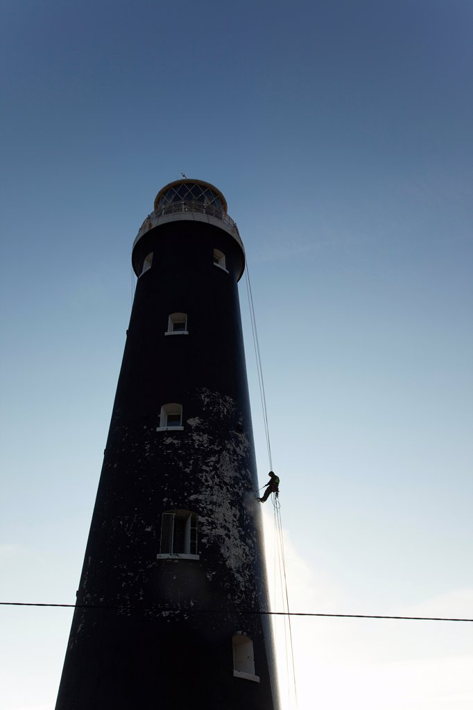 Stock Photo: 1850-46074 England, Kent, Romney Marsh, Dungeness, Man cleaning Lighthouse tower with pressure washer whilst abseiling.