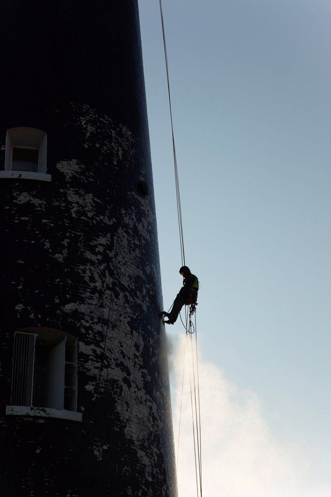 Stock Photo: 1850-46076 England, Kent, Romney Marsh, Dungeness, Man cleaning Lighthouse tower with pressure washer whilst abseiling.