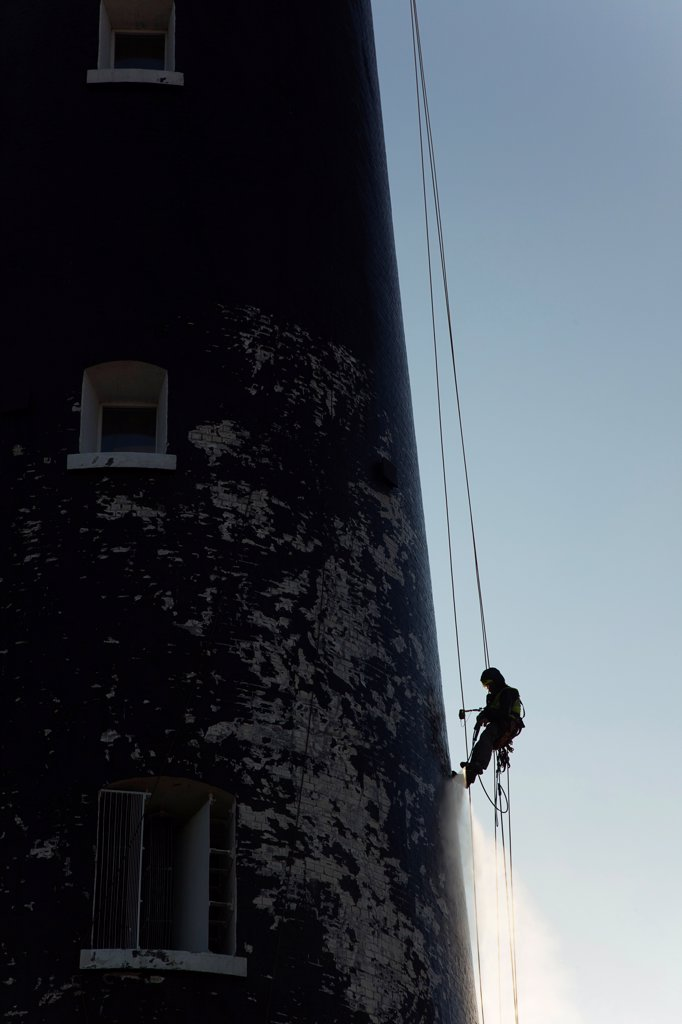Stock Photo: 1850-46078 England, Kent, Romney Marsh, Dungeness, Man cleaning Lighthouse tower with pressure washer whilst abseiling.