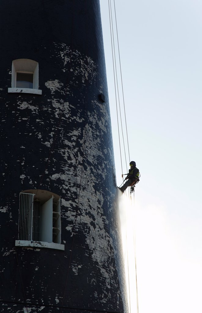 England, Kent, Romney Marsh, Dungeness, Man cleaning Lighthouse tower with pressure washer whilst abseiling. : Stock Photo