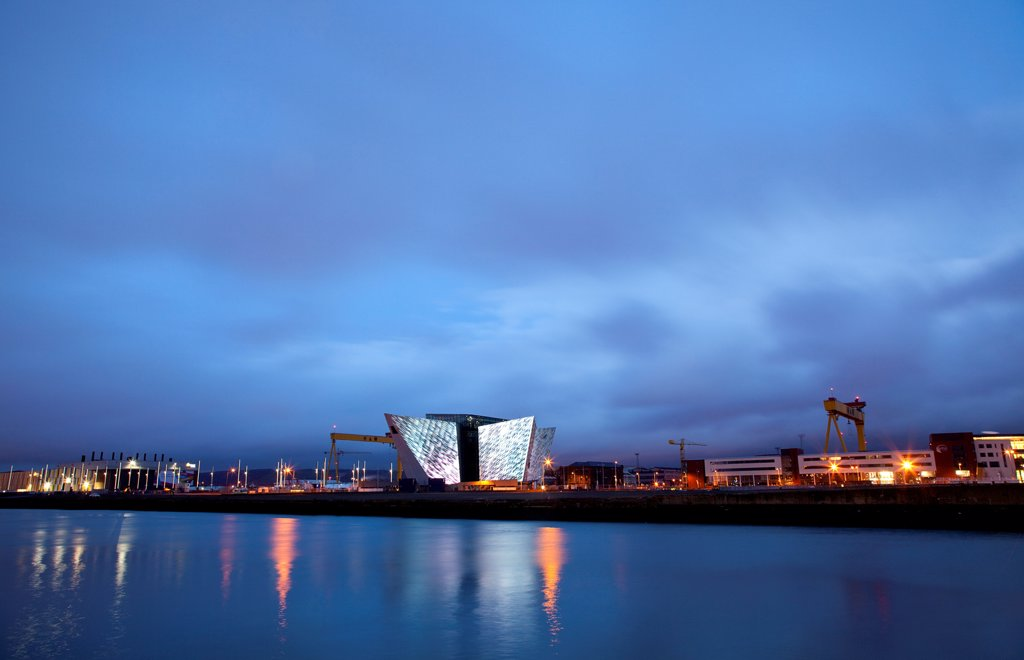 Ireland, North, Belfast, Titanic Quarter, Visitor centre designed by Civic Arts & Eric R Kuhne, illuminated at night. : Stock Photo