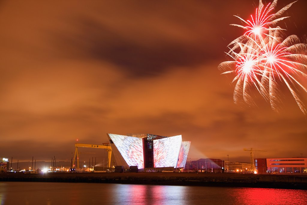 Ireland, North, Belfast, Titanic Quarter, Visitor centre designed by Civic Arts & Eric R Kuhne, illuminated during opening fireworks and projection display. : Stock Photo