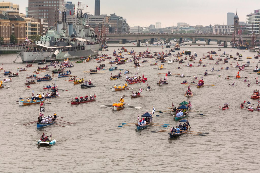 Stock Photo: 1850-46388 England, London, Flotilla of small rowing boats proceed along River Thames past HMS Belfast as part of the Queens Thames Diamond Jubilee Pageant, taken from Tower Bridge, 3rd June 2012.