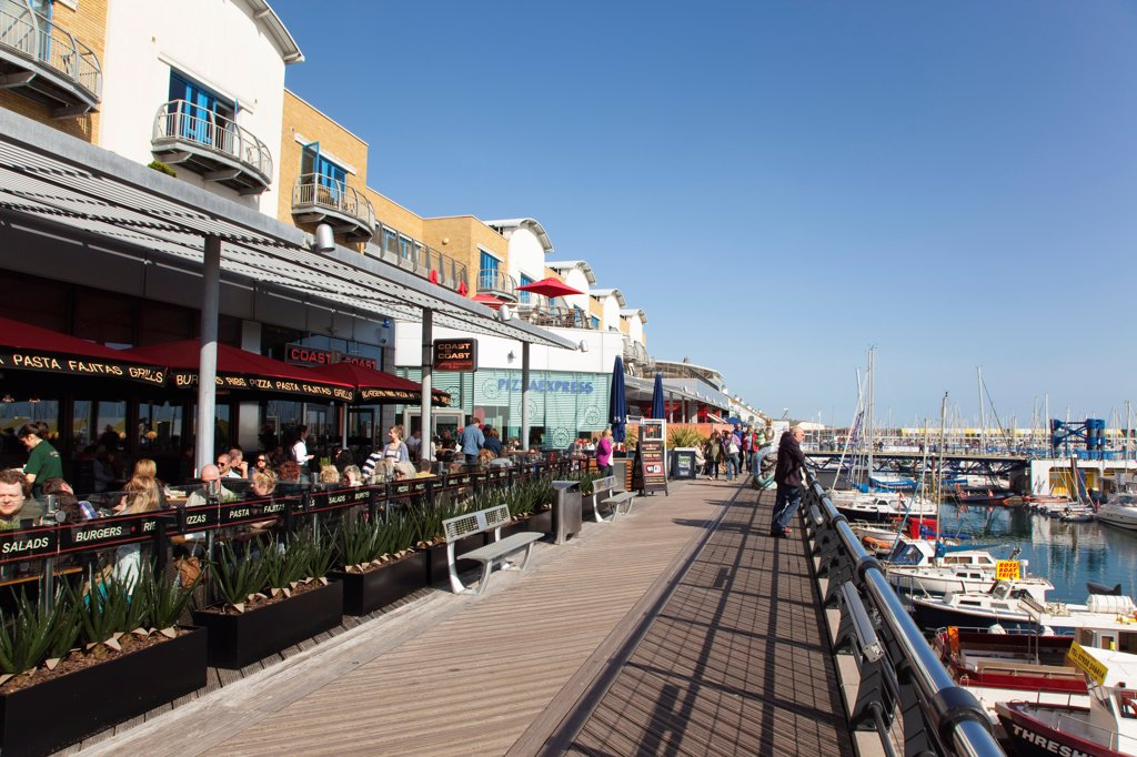 Stock Photo: 1850-46391 England, East Sussex, Brighton, View along the boardwalk over boats moored in the Marina.