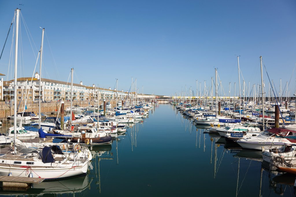 Stock Photo: 1850-46399 England, East Sussex, Brighton, view over boats moored in the Marina with apartment buildings behind.