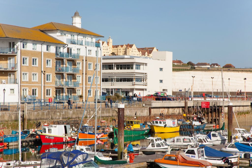 England, East Sussex, Brighton, view over fishing boats moored in the Marina with apartment buildings behind. : Stock Photo
