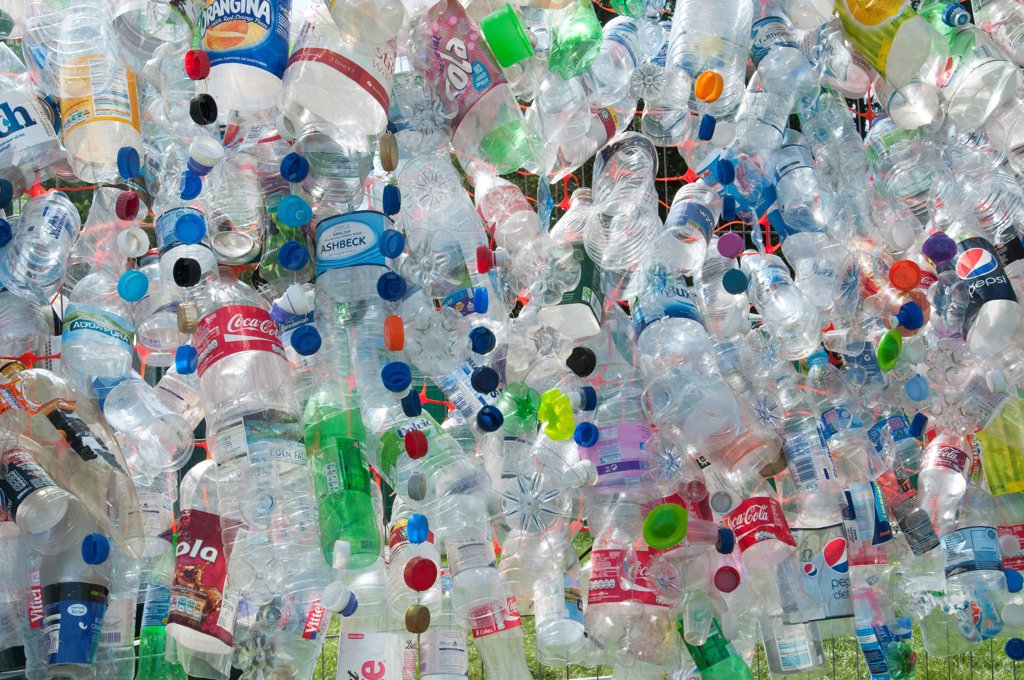Environment, Recycling, Plastic bottles attached to a wire fence at the WOMAD festival, to highlight the need to recycle non-sustaninable materials. : Stock Photo