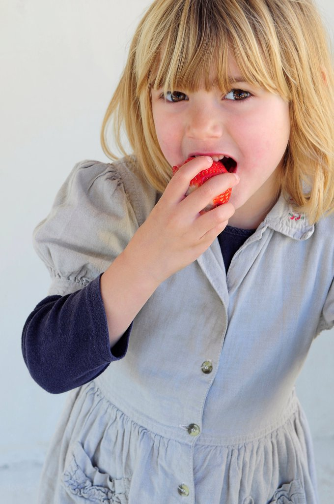 Stock Photo: 1850-46465 Kids, Eating, Fruit, 5 year old Eva eating first strawberries of the year in February.