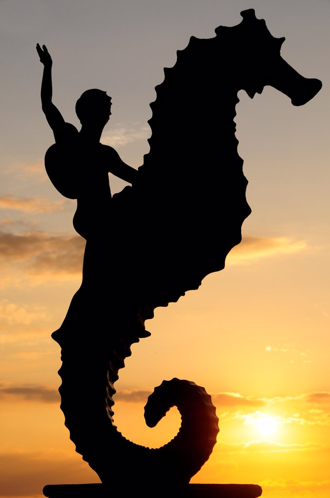 Stock Photo: 1850-46641 Mexico, Jalisco, Puerto Vallarta, Caballeo del Mar sculpture of boy riding a seahorse by Rafel Zamarripa silhouetted on the Malecon at sunset.