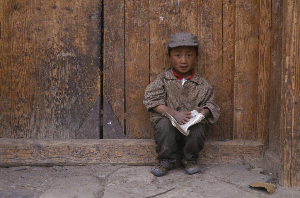 China, Gansu, Xiahe, Young Tibetan Boy Reading A Book : Stock Photo