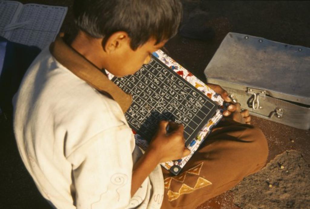 India, Maharashtra, Nasik, School Boy Using Chalk And Slate : Stock Photo