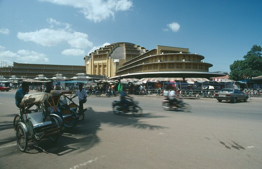 Cambodia, Phnom Penh, Trishaws And Motorcyclists On Road In Front Of The Central Market Buildings. : Stock Photo