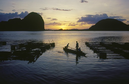 Thailand, Phang Nga, Fish Farm At Sunset With Two Men In A Canoe : Stock Photo