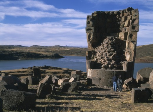 Stock Photo: 1850-5256 Peru, Puno Administrative Division, Puno Area, 'Sillustani.  Pre Columbian Funeral Tower, Or Chullpa, With Two People Standing At It?s Base, Looking Upwards.  '