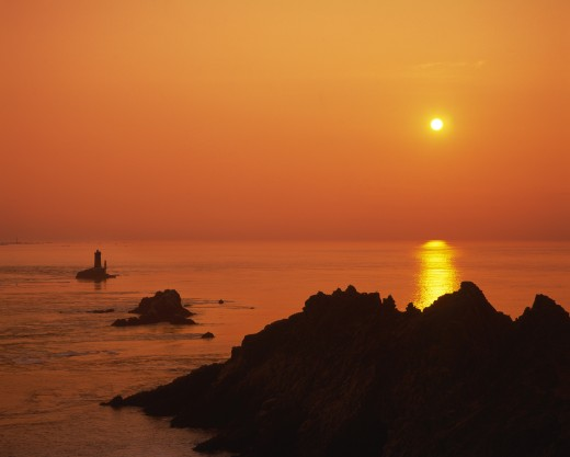 France, Brittany, Finistere, Near Audierne.  Pointe Du Raz At Sunset.  Rocks Silhouetted Against An Orange Sun And Evening Sky Reflected In The Water. : Stock Photo