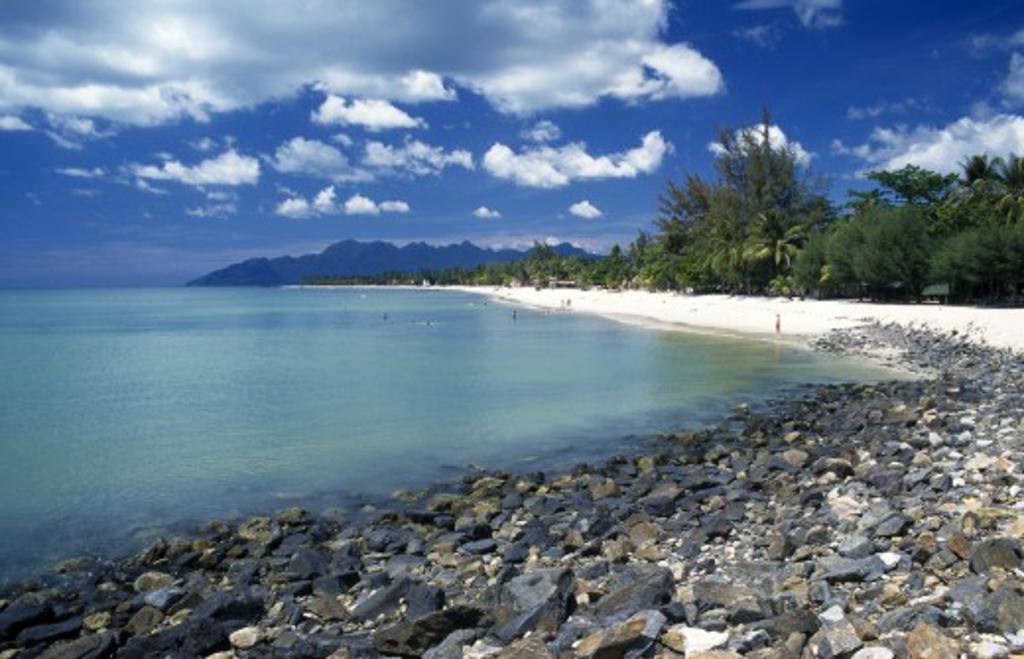 Malaysia, Langkawi, Kedah, Pantai Cenang Beach Looking Towards Gunung Mat Cincang With A Stoney Beach In The Foreground : Stock Photo