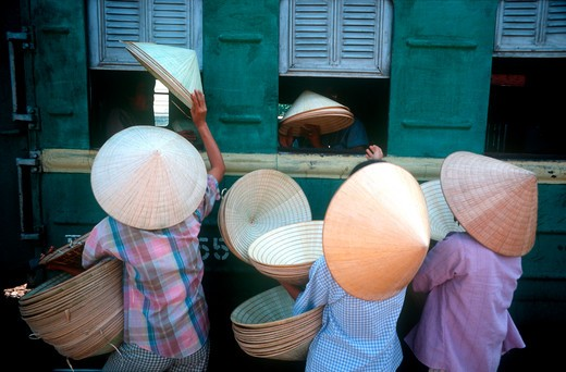 Stock Photo: 1850-5665 Vietnam, Hue, 'Traditional Conical, Straw Hats Being Sold To Train Passengers At Hue Station.'