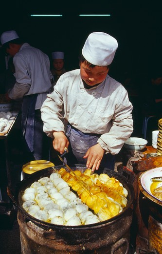 Stock Photo: 1850-5811 China, Shaanxi Province, Xian, Cook Turning Food Frying In Large Pan In Front Of Him.