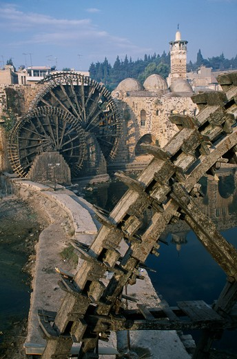 Stock Photo: 1850-5998 Syria, Central, Hama, Wooden Norias Or Waterwheels On The Orontes River And The Al-Nuri Mosque Dating From 1172 And Built Of Limestone And Basalt.  Large Section Of A Wheel In The Immediate Foreground.