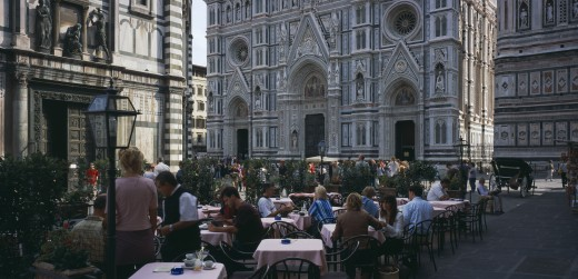 Italy, Tuscany, Florence, Cafe In Front Of The Neo-Gothic Marble Facade Of The Duomo With People Sitting At Outside Tables Having Coffee And Reading Guide Books. : Stock Photo
