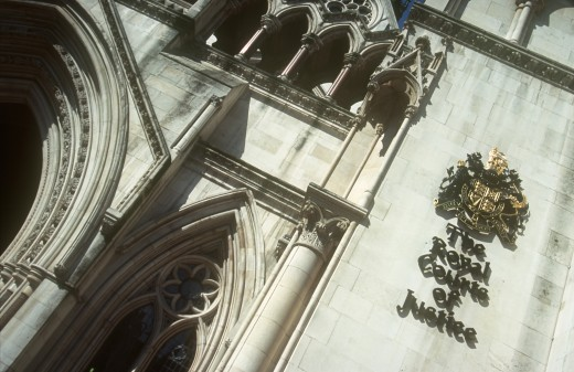 England, London, Royal Courts Of Justice. View Looking Up At The Building With The Crest Displayed On The Wall. : Stock Photo
