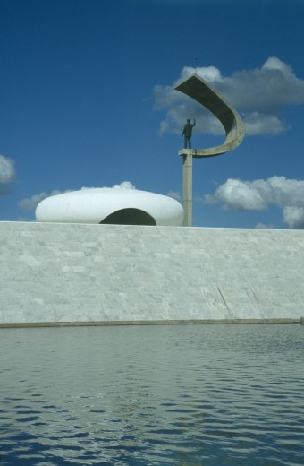 Brazil, Federal District, Brasilia, Kubitschek Memorial With Large Sculpture Holding A Statue Seen Over Surrounding Pool : Stock Photo