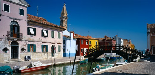Stock Photo: 1850-6910 Italy, Veneto, Venice, 'Burano Island.  Bridge And Canal With Boats Moored To Posts Along Each Side Overlooked By Pink, Blue, Red And Yellow Buildings And Bell Tower Behind.'