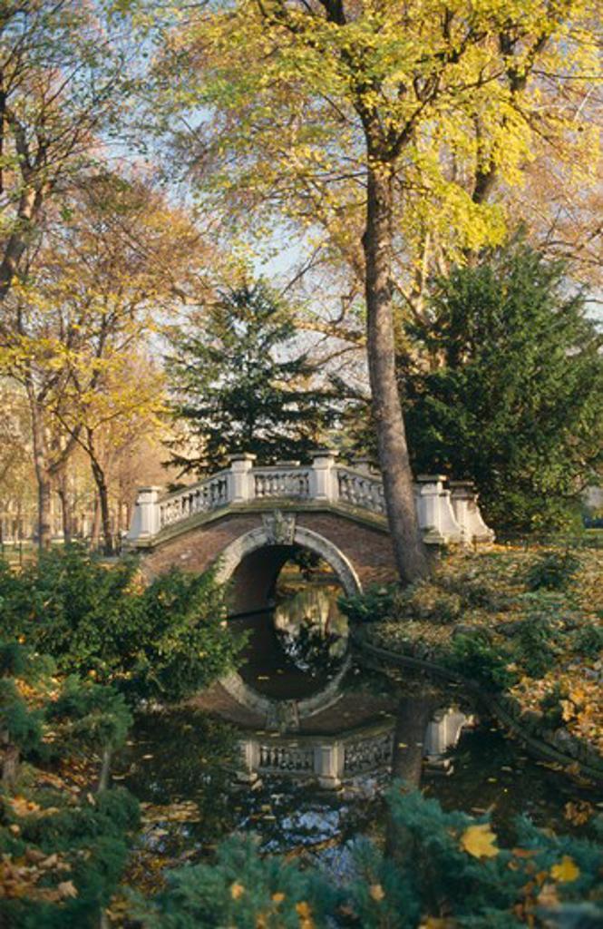 France, Ile De France, Paris, Parc Monceau Created By Landscape Designer Louis Carmontelle.  Arched Bridge Over Stream Surrounded By Trees. : Stock Photo