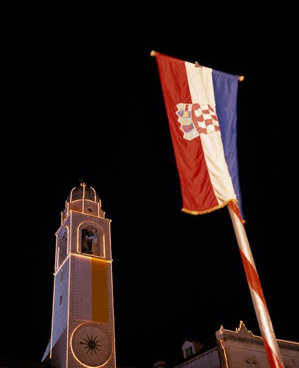 Stock Photo: 1850-7964 Croatia, Dalmatia, Dubrovnik, View Looking Up At The Clocktower Illuminated At Night With Croatian Flag In The Foreground