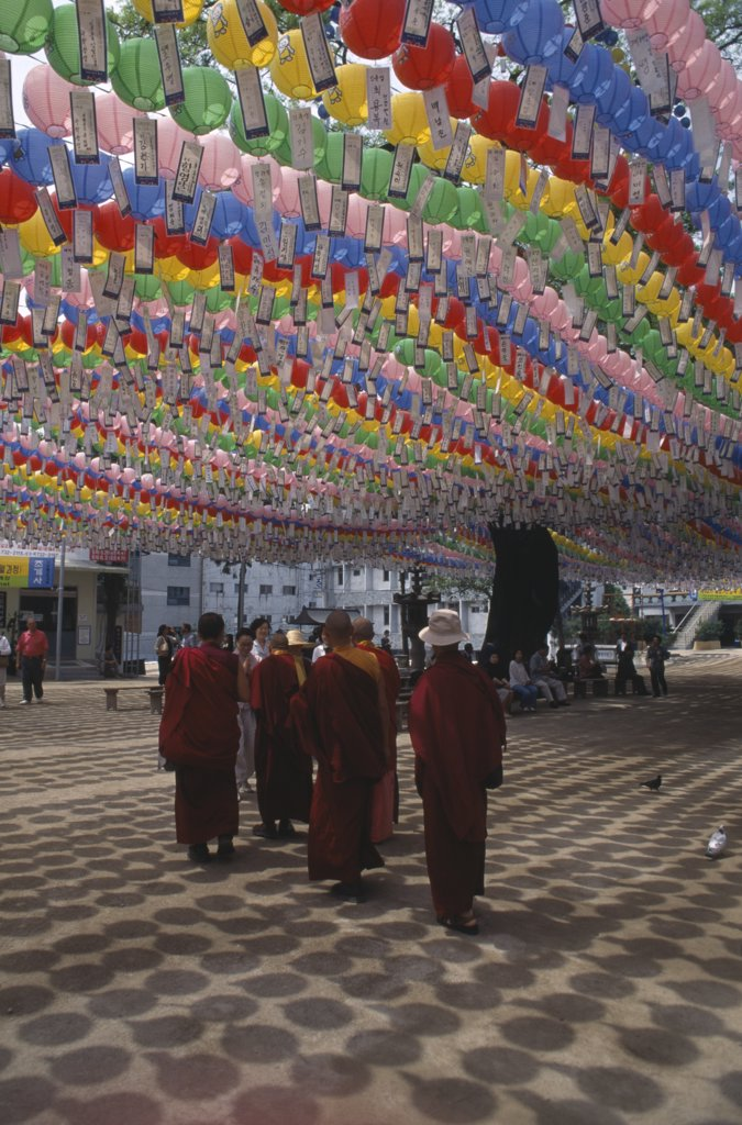 Stock Photo: 1850-8562 South Korea, Seoul, Jogyesa Temple.  Canopy Of Paper Lanterns And Prayer Streamers Hung To Celebrate The Birthday Of Buddha With Group Of Tibetan Buddhist Monks Standing Below.