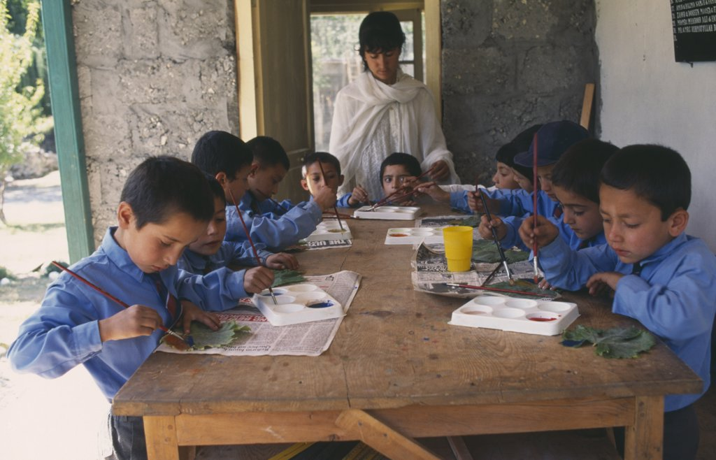 Pakistan, Northern Areas, Sherqillah, Female Teacher At Boys School With Pupils In Art Class. : Stock Photo