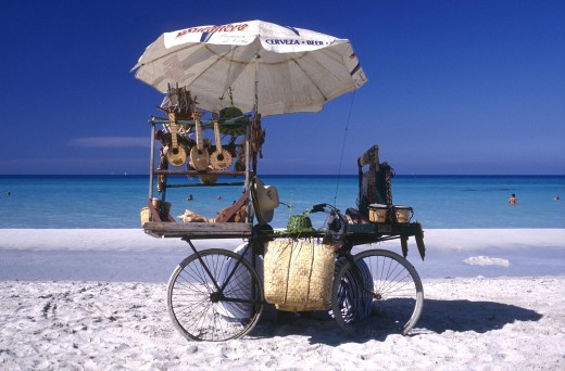 Cuba, Varadero, Beach Vendors Stall On A Bycicle Selling Musical Instruments And Hats With Clear Blue Sea Beyond : Stock Photo