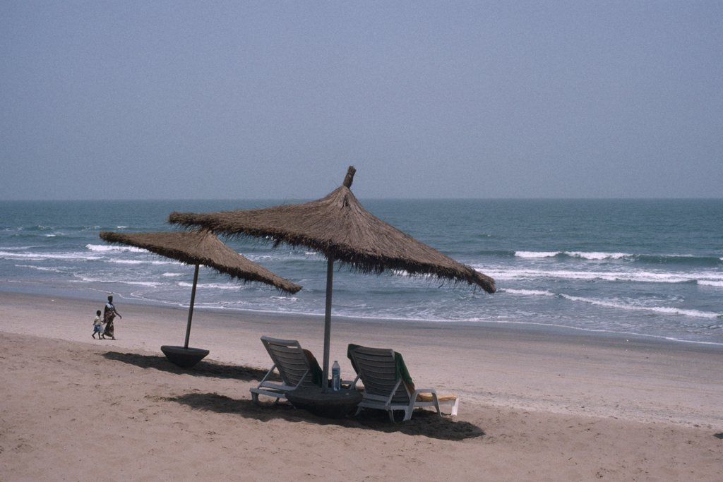 Stock Photo: 1850-9822 Gambia, People, Hotel Beach Front With Woman And Child Walking Hand In Hand Over Sand. Sun Loungers And Parasols In The Foreground