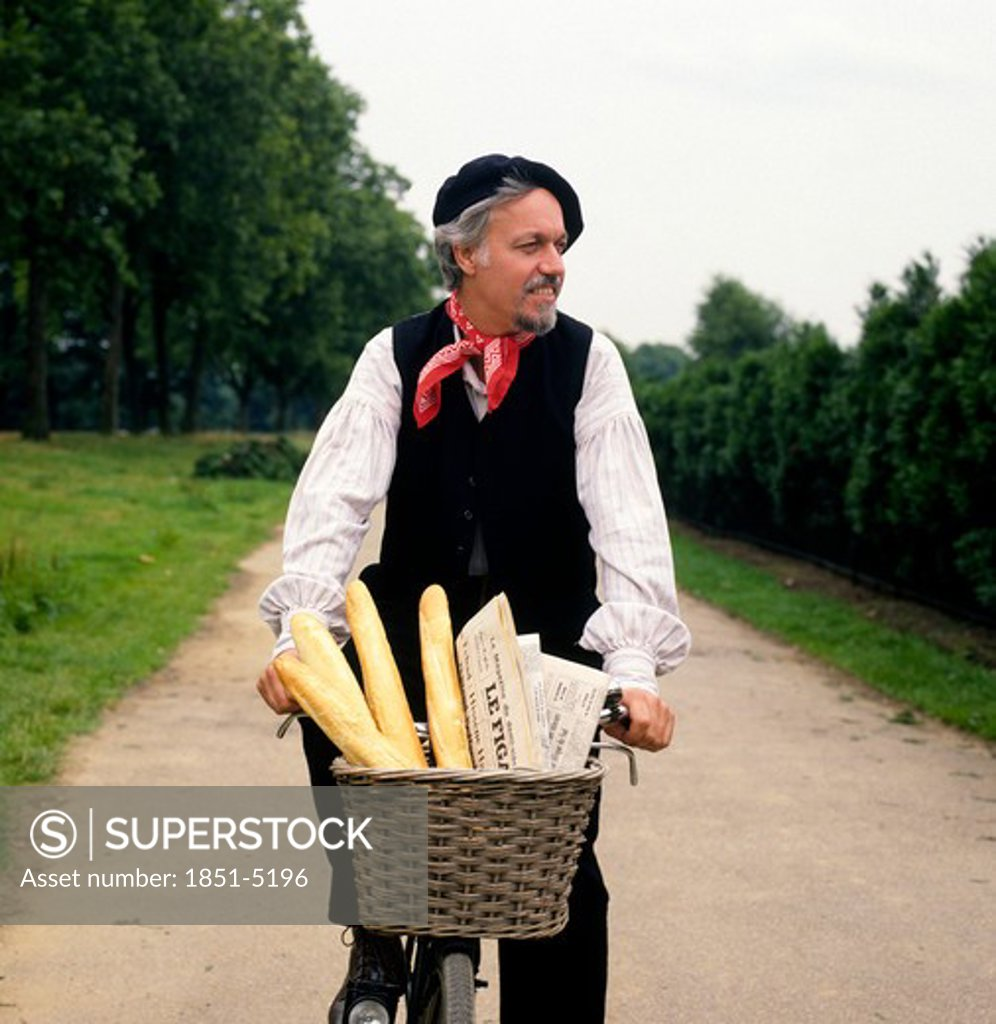 Stock Photo: 1851-5196 Frenchman cycling down country lane with French Bread Baguettes and Newspaper