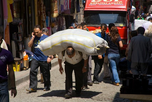 Man carrying a heavy load of goods on his back in Istanbul : Stock Photo