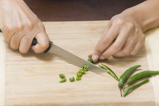 Close-up of a woman chopping green chillies : Stock Photo