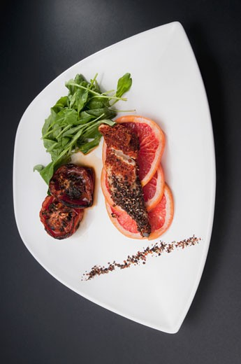 Close-up of pepper coated chops with grapefruit : Stock Photo