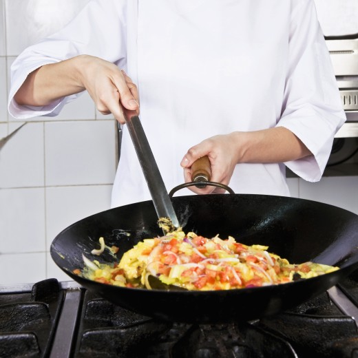 Female chef cooking food in the kitchen : Stock Photo