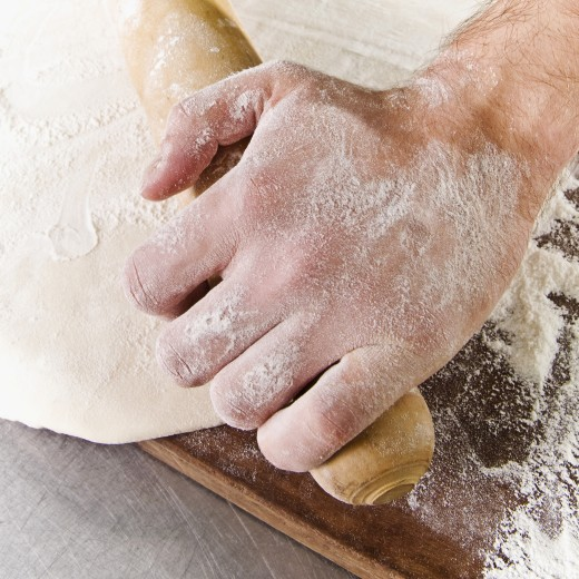 Chef rolling dough with a rolling pin : Stock Photo